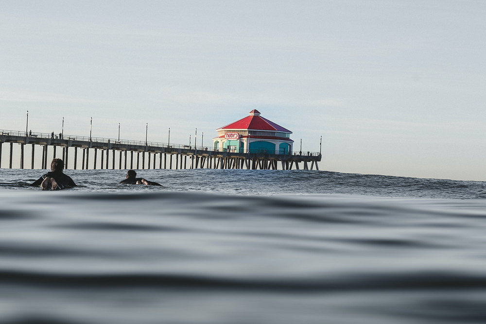 surfers in water with Huntington Beach pier in background