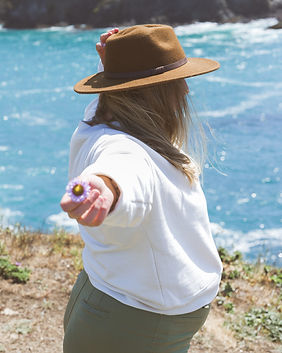 """Travel blogger holding a flower by the ocean. """"Summer 2021 Camping Outfits"""""""