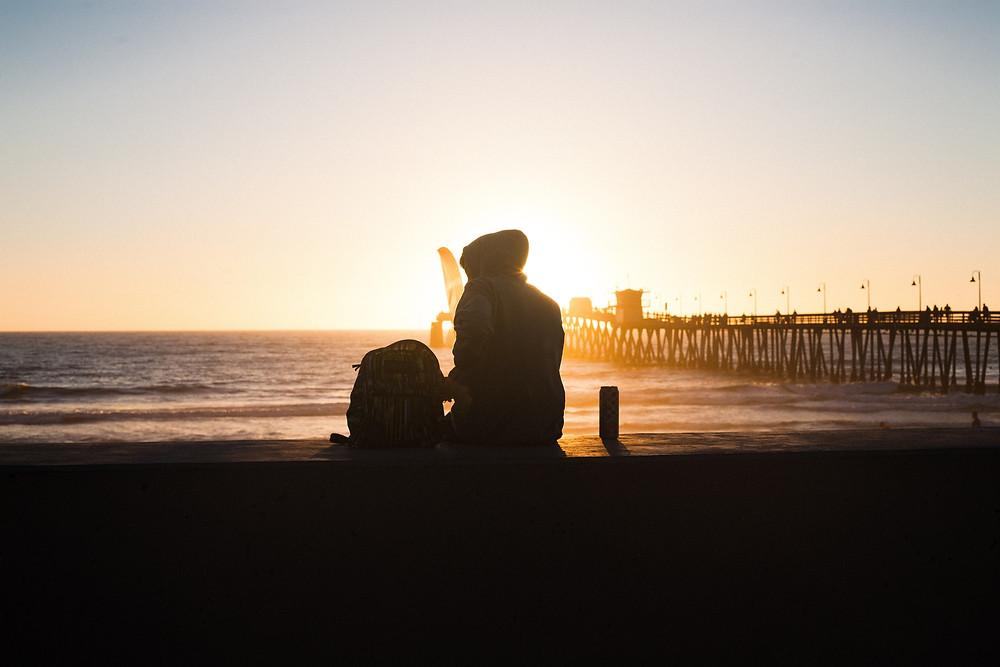 Boy sitting near Imperial Beach Pier at Sunset