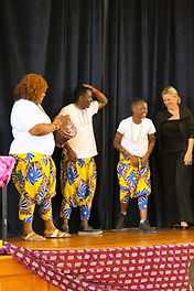 Dancers in traditional African garb on stage