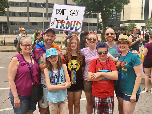 """Deaf Family at Pride with """"Deaf, Gay, and Proud"""" Sign"""