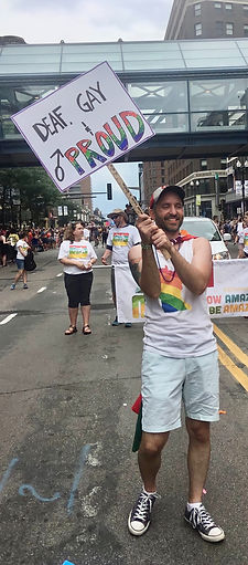 """man marching in pride parade with """"Deaf, Gay, and Proud"""" sign"""
