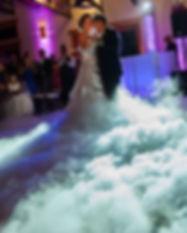 Bride and groom dancing in low lying fog