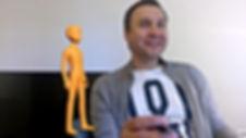 Ein Erwachsenr beim Deutschlernen und ine Mixed-Reality-Figur inorange, die neben ihm schwebt.