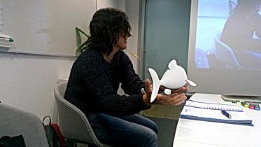 Eine Frau mittleren Alters sitzt im Unterrichtsraum und versucht eine mixed reality Figur zu halten. Es sieht aus als ob ein kleiner Delfin im Raum schwimmt.