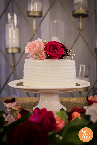 On tier white wedding cake with roses on top