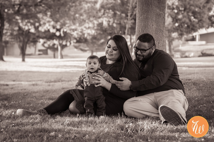 A mom and dad sitting with their baby on the grass
