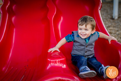 Toddler smiling at the the bottom of a red slide