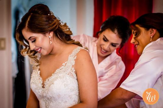Bridesmaids helping the bride zip the dress