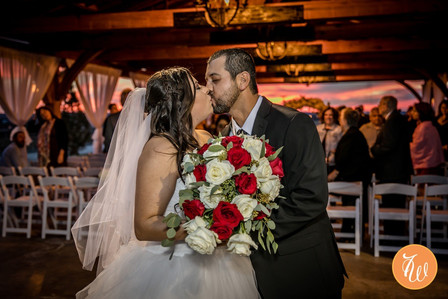 The bride and groom kiss at the end of the aisle