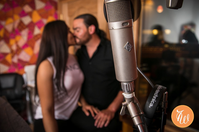 Engaged couple kissing behind a mic