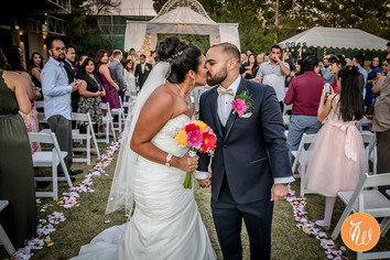 Bride and groom kiss at the end of the aisle