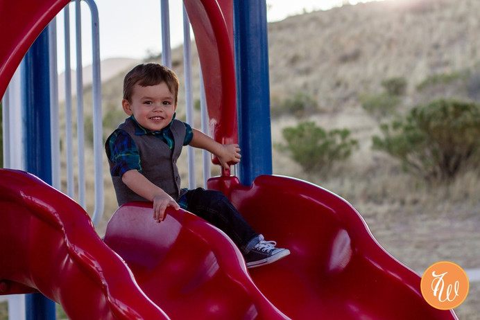 Toddler about to go down a red slide