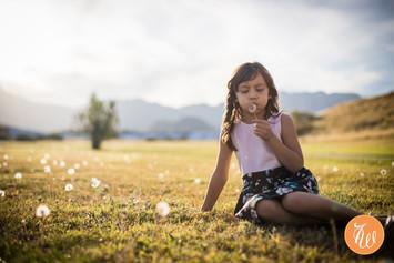 Little girl blowing on a dandelion