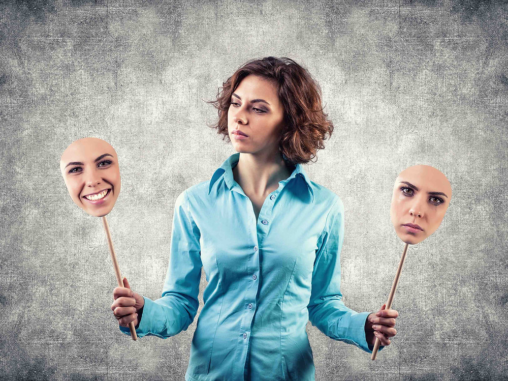 woman holding sticks with faces on the ends with different expressions