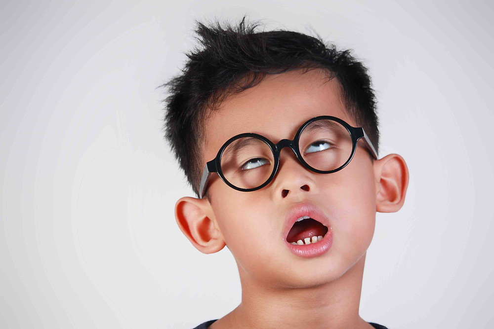 Boy with glasses looking bored from listening to a monotone voice