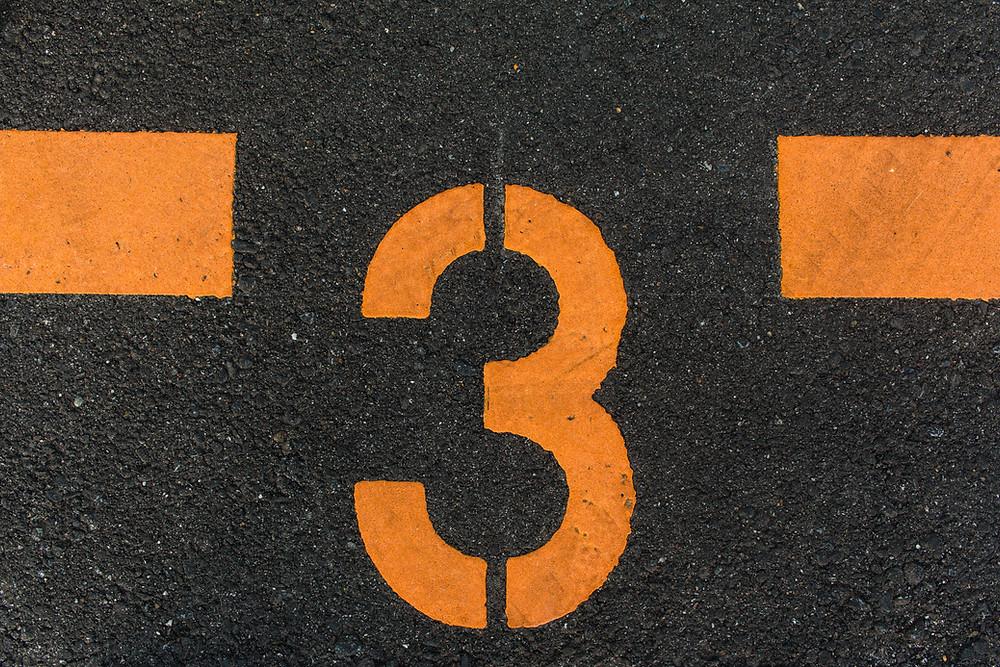 orange number three printed on the ground