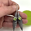 Long Sterling Silver Filigree hollow bead with prong set green peridot on the front. sterling silver earwire