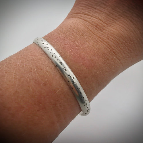 Solid sterling silver cuff bracelet that has been hammered with a dot pattern