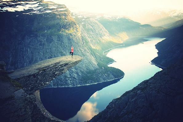 1 woman stands on a rock outcropping in a yoga position overlooking a valley lake between mountains.
