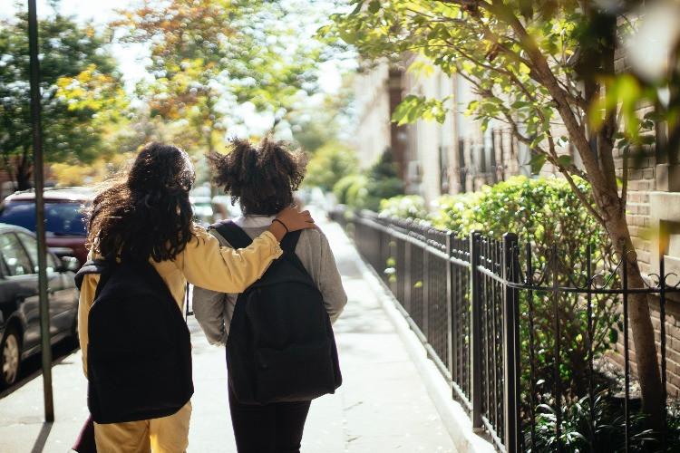Due bambine verso la scuola con lo zaino
