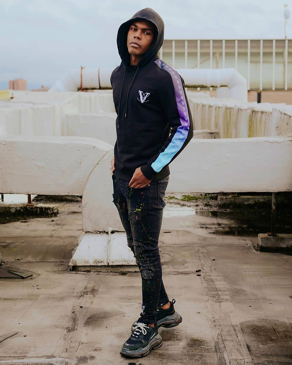 man in hoodie standing in an urban environment.