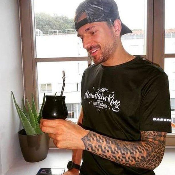 man wearing a black tshirt drinking maté