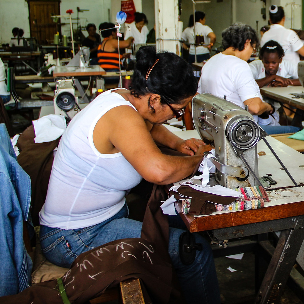 woman in white vest using a sewing machine in a factory