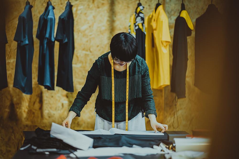 Female pattern cutter constructing a garment