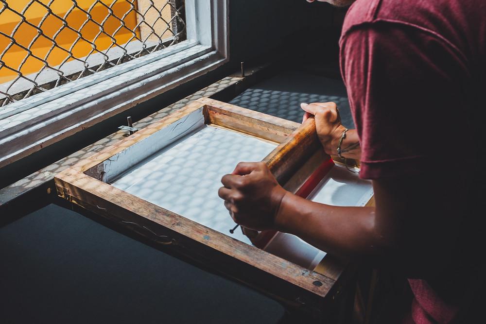 Person screen printing a design