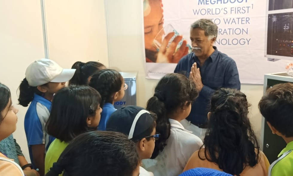 Excited Children keenly listen to Maithri Aquatech's Director Mr. T. M. Shyam Sunder while he Demonstrates and Explains the working process of MEGHDOOT Atmospheric Water Generator at 6th India Water Week 2019