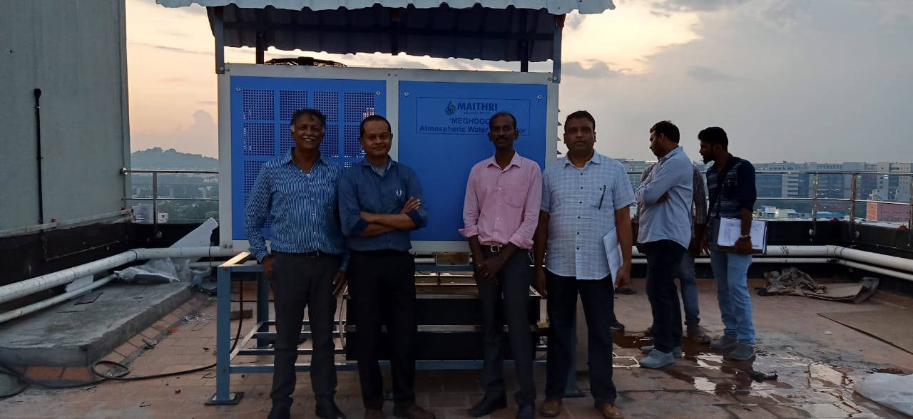 Shyamsunder Mani, Director and Head of Product Development at Maithri Aquatech, stands with the Perficient team, in front of Perficient's MEGHDOOT solution