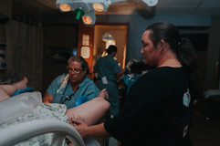 This is a picture of a mother holding her daughter's hand while she pushes during labor at St. Elizabeth Hospital in Lincoln NE