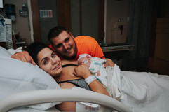 This is a picture of new parents with their baby girl smiling at the camera at St. Elizabeth Hospital in Lincoln NE
