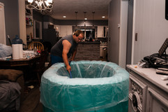 This is an image of a father filling a labor pool with water to prepare for a home water birth in Lincoln NE