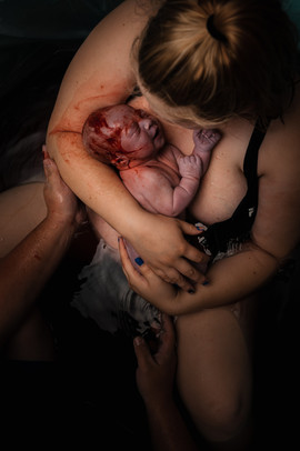 This is an image of a woman holding her baby in the birth pool at her home in Lincoln NE
