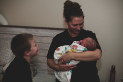Proud brother and doula smile at baby Zavien after his water birth at home in Lincoln, NE