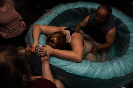 This is an image of a mother surrounded by her birth support team helping her through contractions