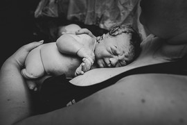 This is a black and white close up of a new baby laying on his mom's chest moments after birth at home in Lincoln NE