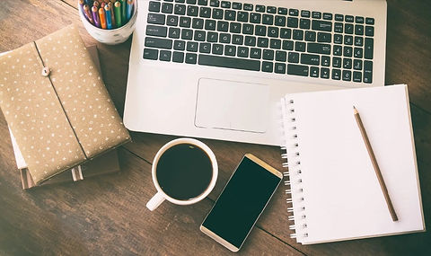 Website image of laptop, jar of coloured pencils, note books, mobile phone, cup of black coffee laying on a wooden table