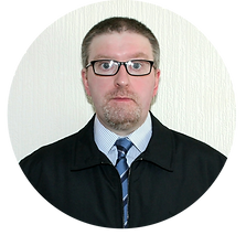 Portrait of SEO web copywriter Eugene Struthers wearing glasses, black jacket, and white shirt, blue and black stripped tie.