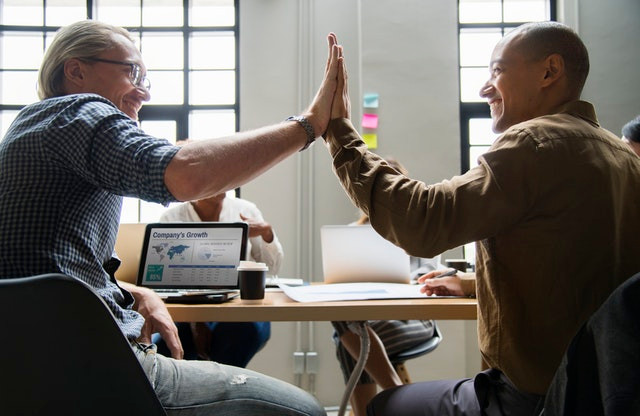 A picture of two colleagues doing a high five at their desk