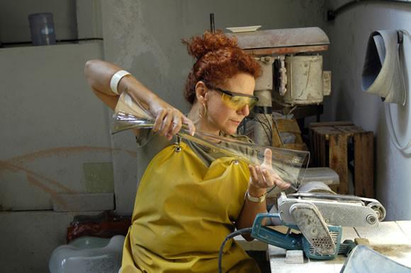 Mulher ruiva de avental segurando peça grande de vidro transparente