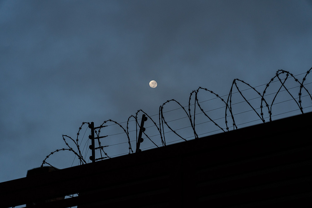 Razor wire, electric fence and full moon