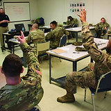 Soldiers in Classroom Raising Hands.png