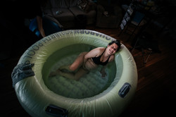 Woman having a contraction in birth pool during home birth delivery.