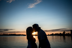 Sunset silhouette of a man and woman kissing at Lake Ontario Park waterfront.