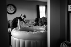 Midwife looking over labouring Mother in a birth pool at a home birth.