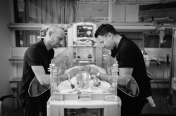 Two Dads looking down at their new baby brought to them through surrogacy in a hospital isolette.