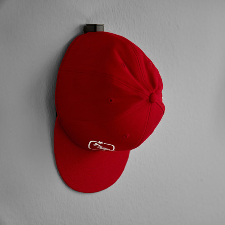 snapback on wall mounted hat hanger by the hat pal.